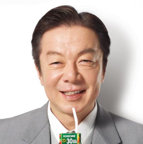 野菜ジュースをもんでいるスーツ姿の古田新太の画像